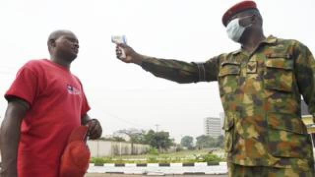 A soldier points a themomoater at a man at the Nigerian Army Reference Hospital in Lagos, Nigeria - Friday 28 February 2020