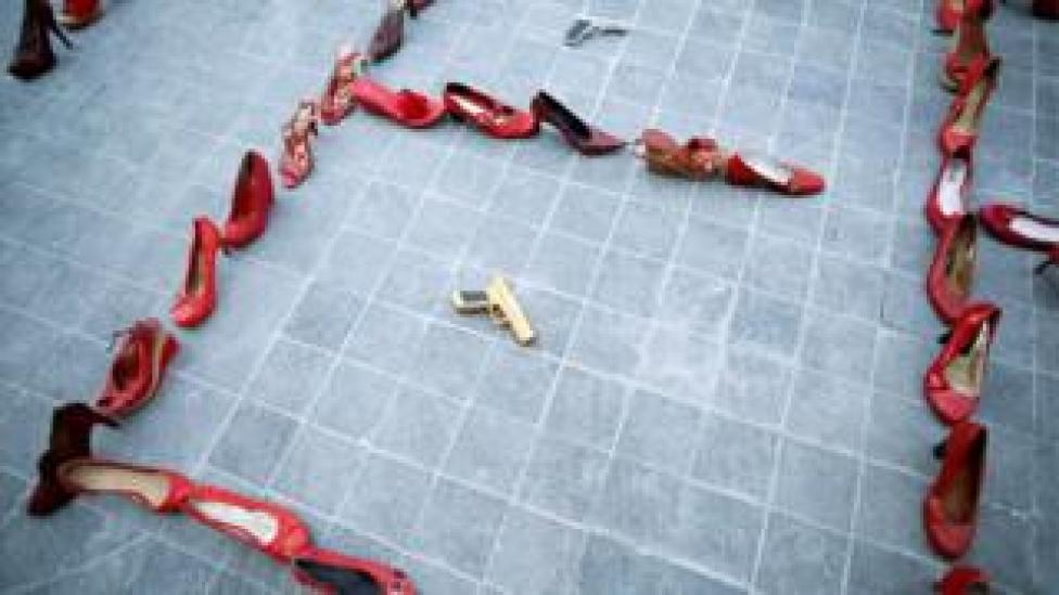 Pairs of women's red shoes are displayed next to a toy gun during the