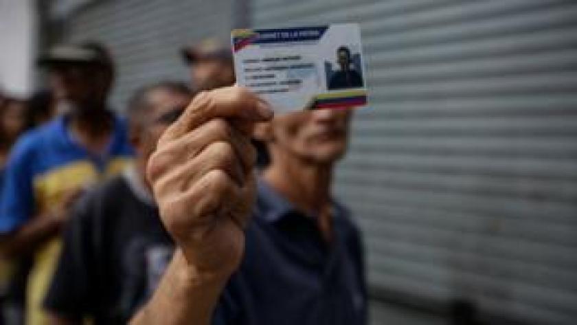 Un venezolano muestra su documento de identidad mientras espera para votar.