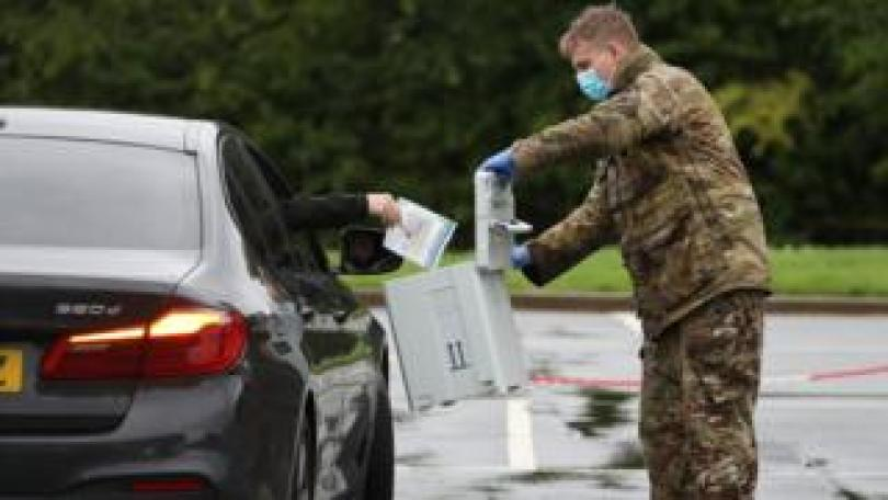 A soldier collects a test from someone through their car window