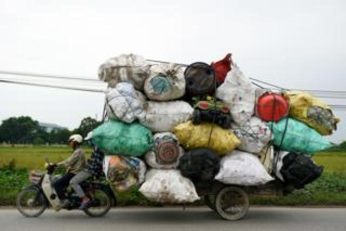 Waste collectors transport plastic scrap for recycling in the suburbs of Hanoi