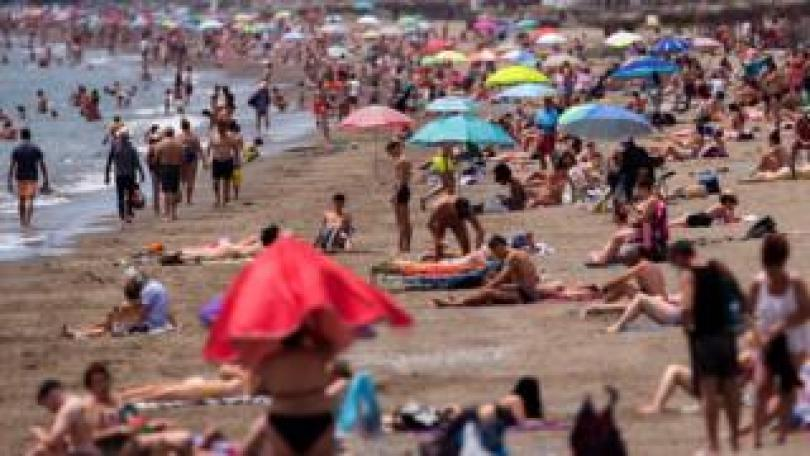 People on a sunny day at the beach in Malaga in June