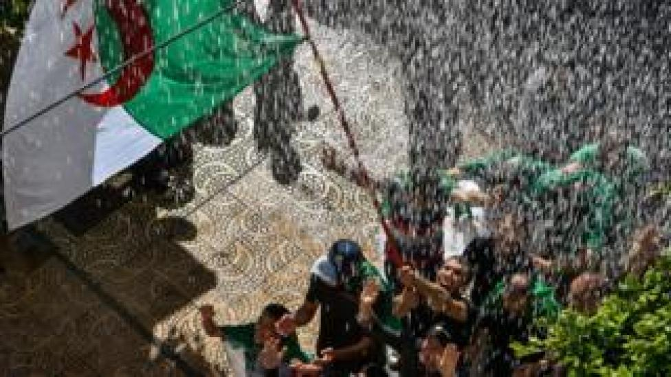 Protesters wave the Algerian flag beneath a shower of water - Friday 10 May