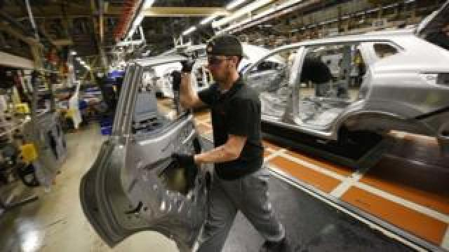 A member of Nissan's manufacturing staff removes a vehicle's door as he works in the 'Trim and Chassis' section of their Sunderland Plant in Sunderland.