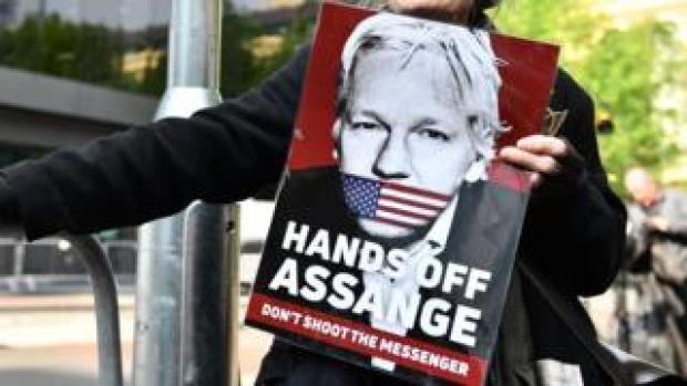 A woman holds up a sign saying: Hands Off Assange, Don't shoot the messenger