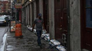 A man walks past sand bags in New Orleans