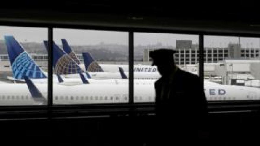 Un piloto, en silueta, camina en aviones de United Airlines mientras se sientan estacionados en las puertas del Aeropuerto Internacional de San Francisco.