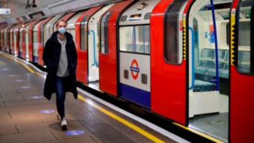 A woman wearing PPE (personal protective equipment), including a face mask as a precautionary measure against COVID-19, walks along the platform alongside a London Underground Tube train in the morning rush hour, on May 11, 2020