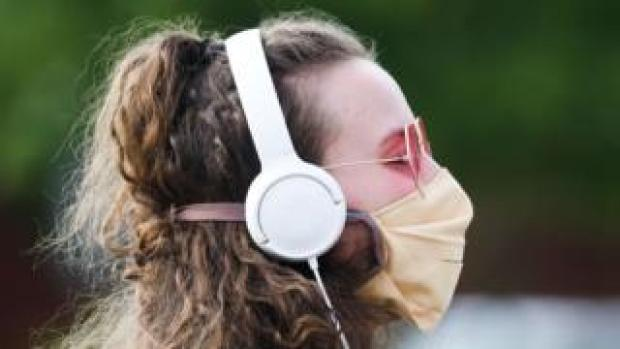 Woman wearing headphones and a mask