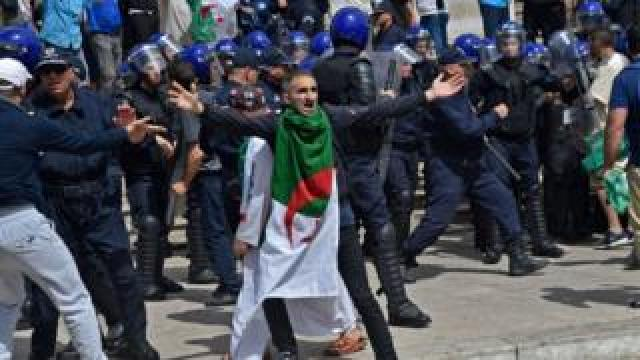 An Algerian protester reacts during an anti-government demonstration outside La Grande Poste (main post office) in the centre of the capital Algiers on May 17, 2019. - Thousands of Algerians pushed through police tear gas and water cannon in the capital, to rally at the focal point of mass protests against the country's ruling elite. Riot police for hours prevented demonstrators from marching on the iconic central post office, with officials citing security concerns, but they ultimately gave way under pressure from the crowds.