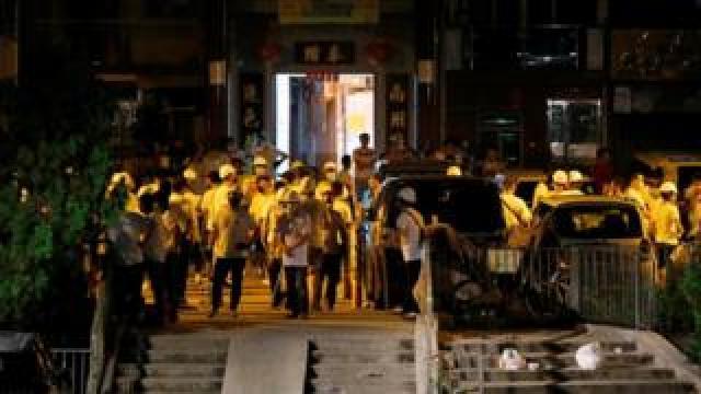 Crowd of men in white T-shirts at Yuen Long MTR station in Hong Kong