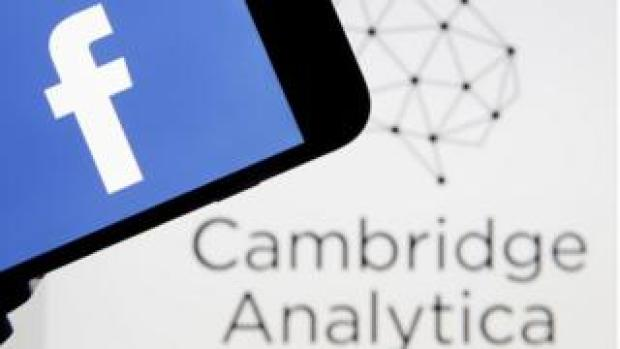 The Facebook logo is seen on a smartphone in front of a Cambridge Analytica logo in this composite shot