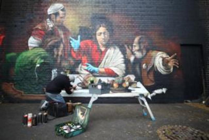 An artist paints a mural depicting the Supper at Emmaus by Caravaggio