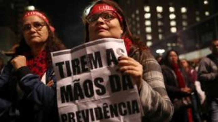 """Demonstrators protest against President Jair Bolsonaro's proposed pension reform project in Sao Paulo, Brazil, July 10, 2019. The sign reads """"Take your hands off the pension""""."""