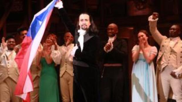 Lin-Manuel Miranda standing on-stage at the end of a performance of Hamilton, holding the Puerto Rico flag