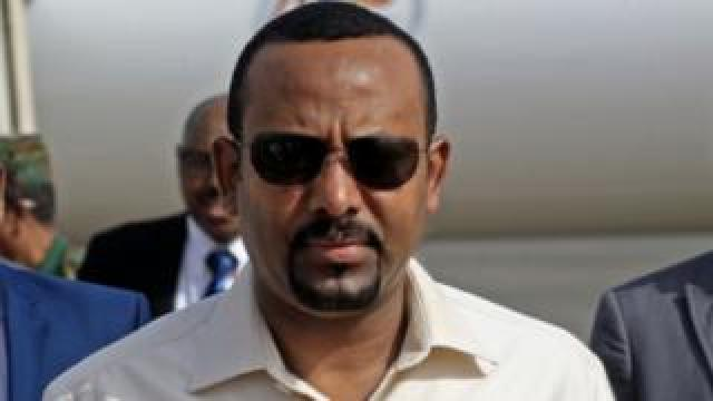 """In this file photo taken on June 07, 2019 Ethiopia""""s Prime Minister Abiy Ahmed (C) arrives at Khartoum international airpor"""