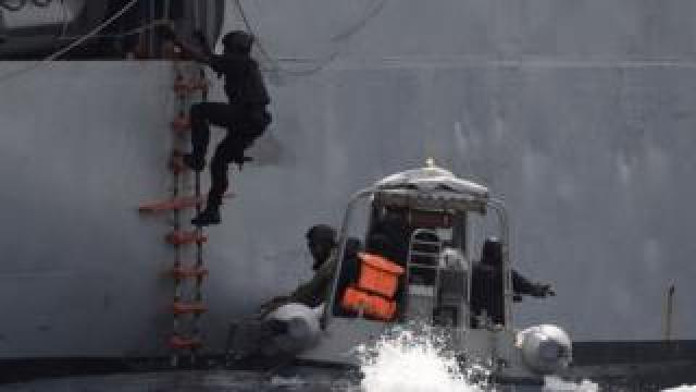 A Nigerian special forces officer climbs aboard a vessel during an anti-piracy exercise, March 2019