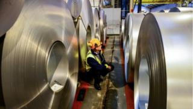worker inspects rolls of steel
