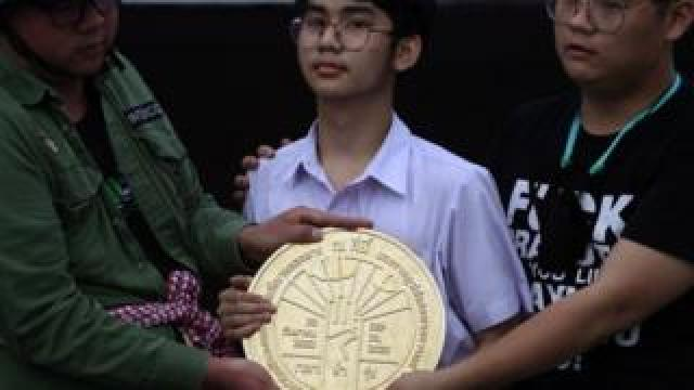 """Student leaders install a plaque declaring """"This country belongs to the people"""" during a mass rally"""