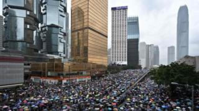 Protesters shelter under umbrellas during a downpour as they occupy roads near the government headquarters in Hong Kong on June 12, 2019.
