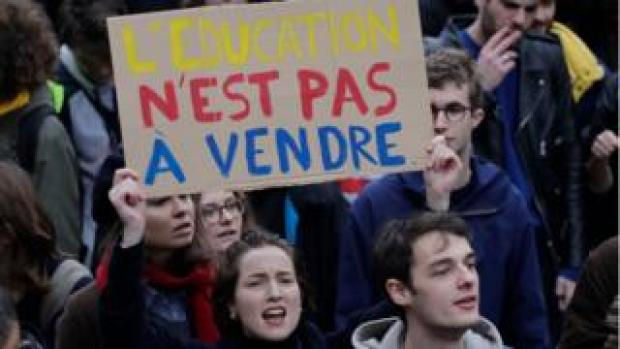 A girl shouts as she brandishes a placard reading 'Education is not for sale' as students demonstrate against French government Education reforms on December 6, 2018 in Paris