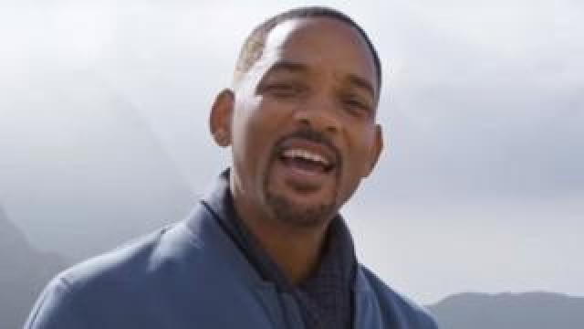 Will Smith standing by some mountains
