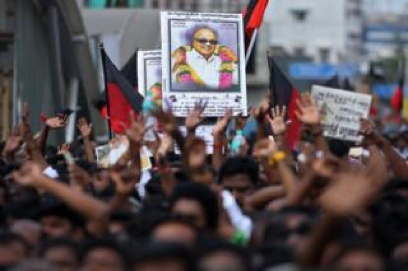Supporters hold the portrait of M Karunanidhi during his funeral in Chennai on 8 August 2018.