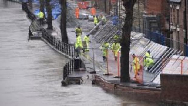 Environment Agency teams work on temporary flood barriers in the Wharfage area of Ironbridge, Shropshire