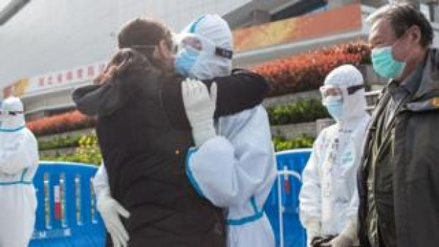 A woman (L) who recovered from COVID-19 hugs a medical staff member before leaving a temporary hospital set up to treat people with the COVID-19 coronavirus in Wuhan, China, on 10 March, 2020.