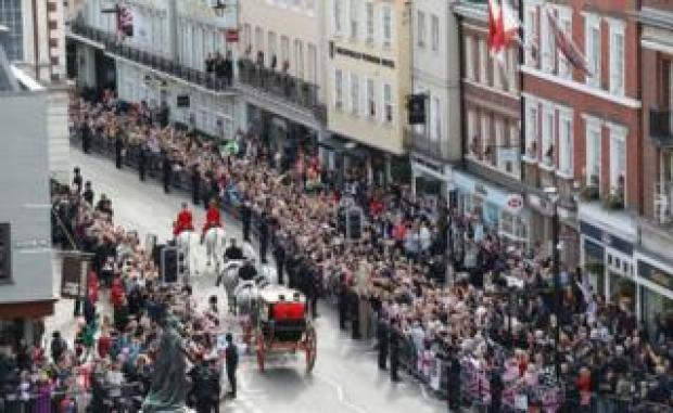 Crowds cheer Jack Brooksbank and Princess Eugenie as they embark on a carriage ride following their wedding at Windsor Castle