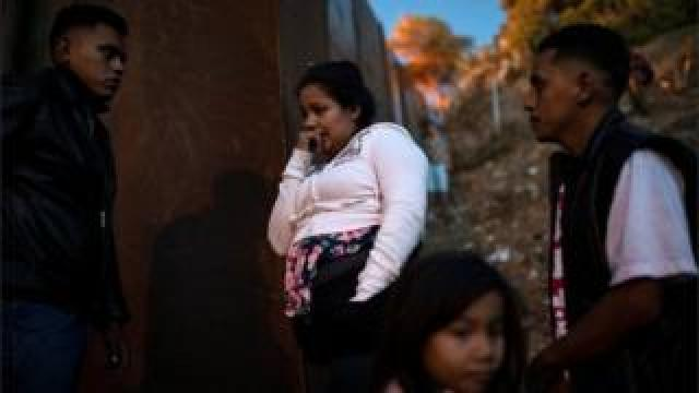 Migrants from Honduras stand by the border fence in Tijuana, Mexico on 2 December, 2018