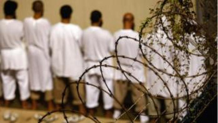 Detainees stand during an early morning Islamic prayer at the U.S. military prison for 'enemy combatants' on October 28, 2009 in Guantanamo Bay, Cuba.