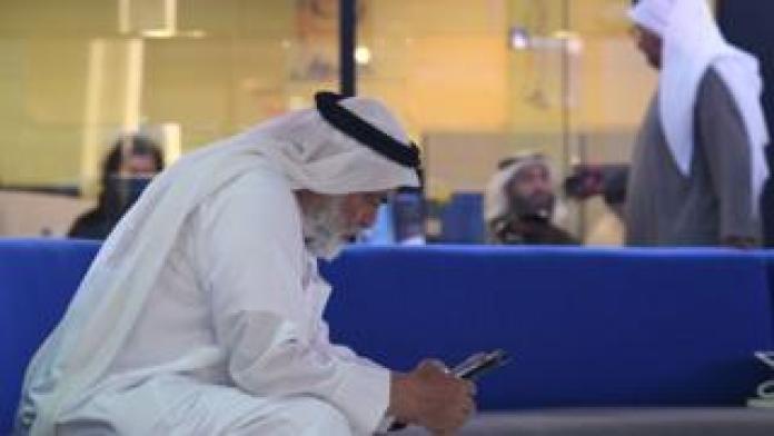 Man in Dubai uses a mobile phone