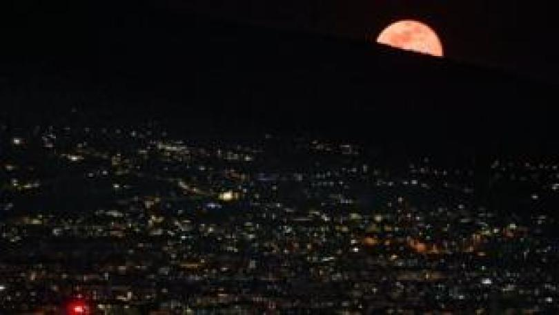 The red supermoon rises behind Mt Vesuvius as seen from Naples, Italy