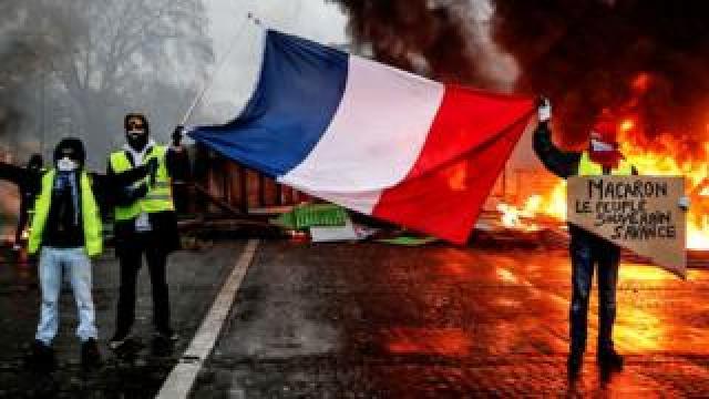 Betogers het 'n Franse vlag in 'n brandende barricade in Parys gehou op 'n vlak van 'n sug geel baadjies