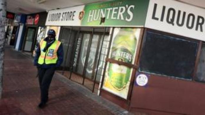Police officer outside a liquor store in Cape Town