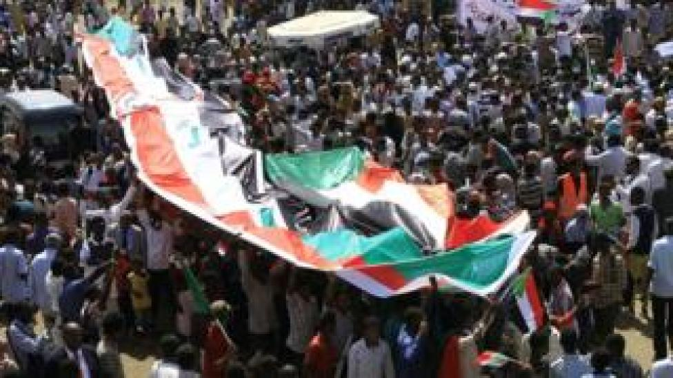 Sudanese protesters deploy their national flag as they protest outside the army headquarters in Khartoum