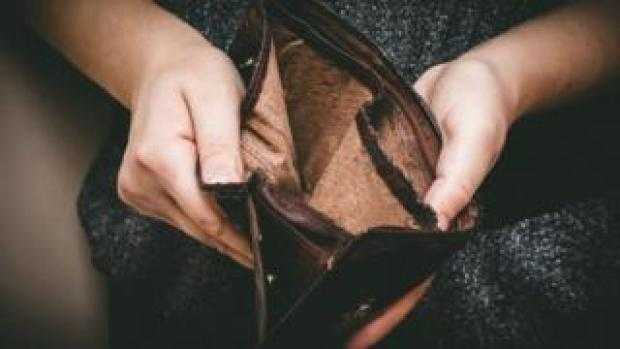 A woman holds an empty wallet in her hands