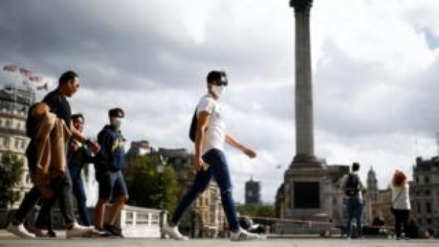 People wearing protective face masks walks through Trafalgar Square