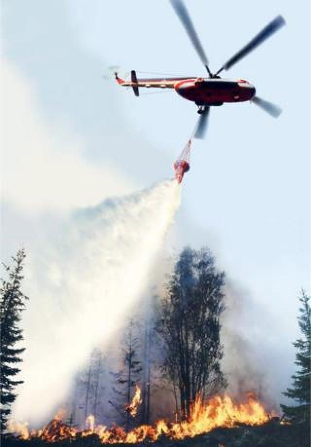 A helicopter dumps water to extinguish wildfires in Krasnoyarsk region, Russia. Photo: 1 August 2019