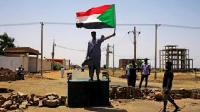 "A Sudanese protester holds a national flag as he stands on a barricade along a street, demanding that the country""s Transitional Military Council hand over power to civilians, in Khartoum, Sudan June 5, 2019."