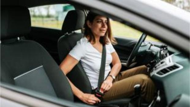A woman putting on a seat belt