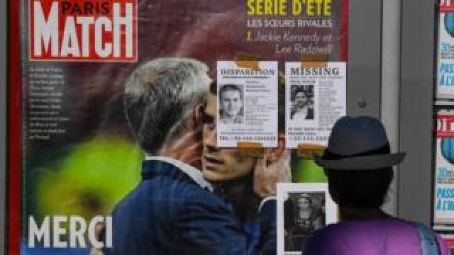 A woman looks at portraits of missing victims of the Bastille Day terror attack on the Promenade des Anglais on July 16, 2016 in Nice, France.