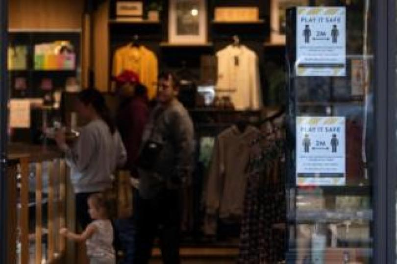Posters promoting social distancing are displayed in a shop window in Christchurch on 14 May, 2020
