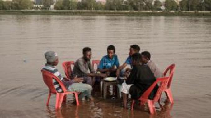Sudanese men share a meal in the shallows waters of the Tuti island, where the Blue and White Nile merge in Khartoum, on June 24, 2019.