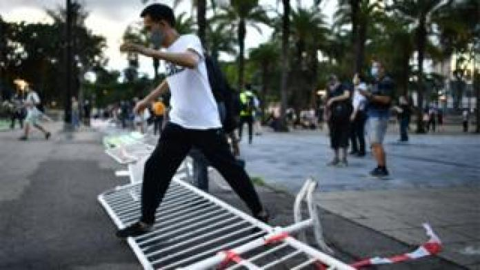 A man steps over a barricade which had been set up to block access to Victoria Park in Hong Kong on June 4, 2020