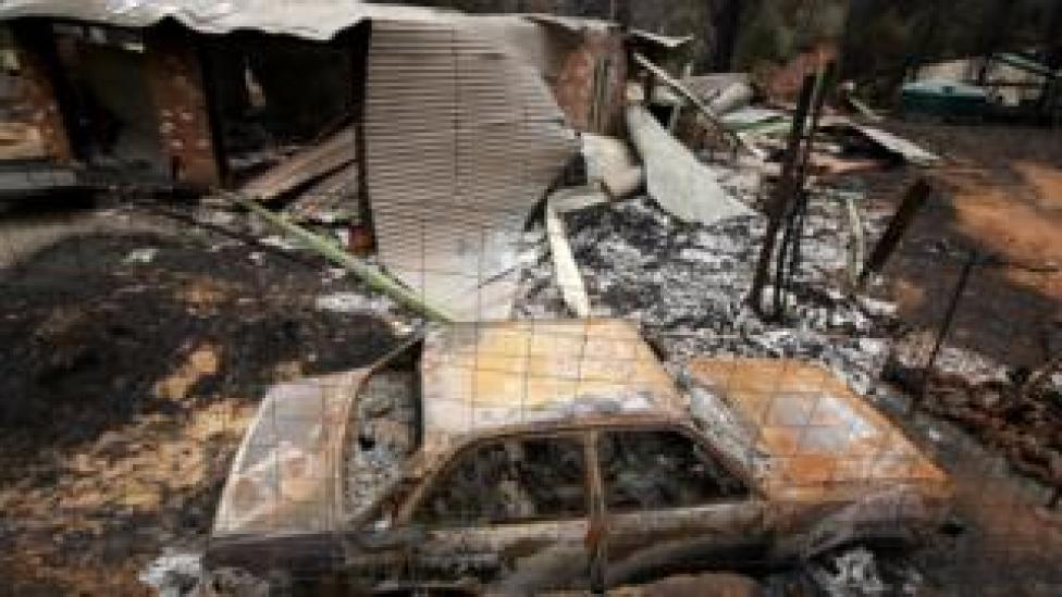 The charred remains of a car and a house following a bushfire in Kinglake in Victoria