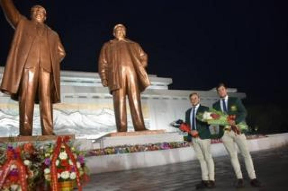 Two Australians pose for a photo in front of a monument in North Korea