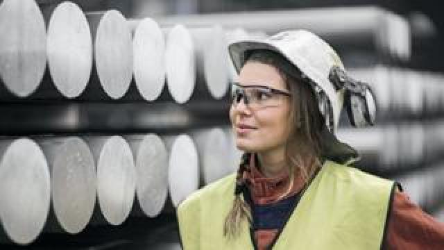 Female Norsk Hydro worker standing in front of aluminium tubes