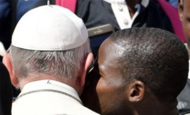 A member of a rugby team kisses Pope Francis